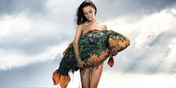 Привлекательная женщина держит рыбу в руках